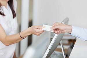Man handing woman a credit card