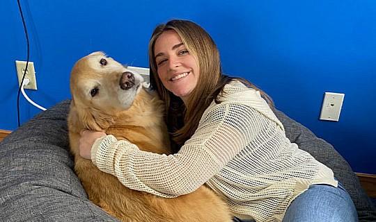 Whiteboard Marketing team member hugging a dog at work